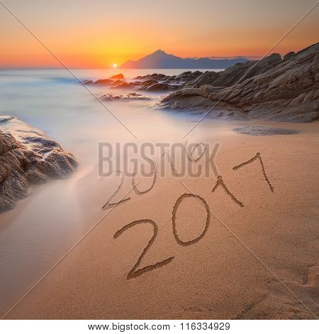 Digits 2016 And 2017 On Coast Sand At Beautiful Sunrise