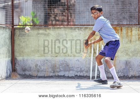 KOLKATA, INDIA - APRIL 14, 2013: Poor indian boy ready to make a beat in the cricket game
