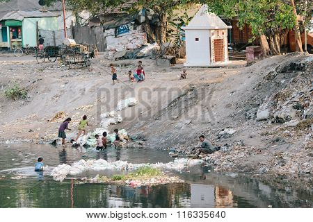 KOLKATA, INDIA - APRIL 12, 2013: Poor indian children work by sorting garbage in the stinky river