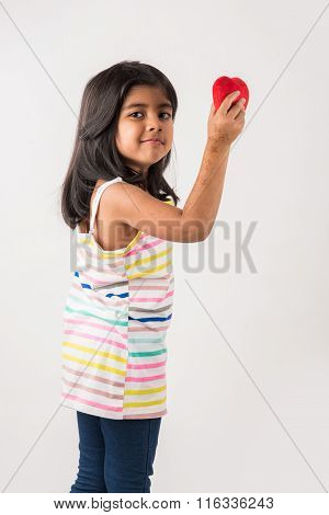 small girl with stuffed heart, stuffed heart and girl, indian girl holding stuffed heart, asian girl