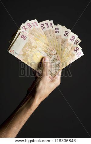 Human hand holding money fan