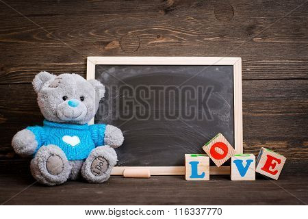 chalk board and  teddy bear on a wooden background