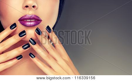 Beautiful girl showing black manicure nails .
