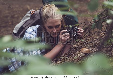 Woman With Vintage Camera Lying On Forest Floor Observing Mushroom.