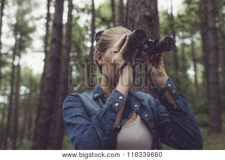 Young Woman In Forest Observing With Binocular.
