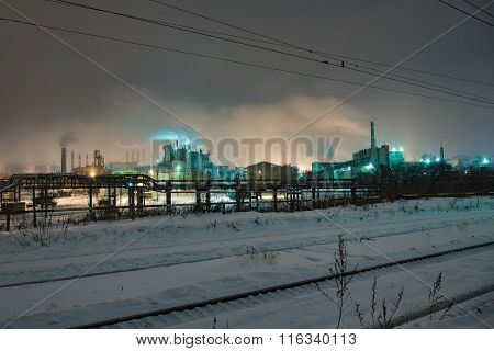 Power station with steam cloud blown by the wind in a cold starry winter night