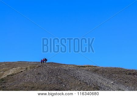 Family Traveling On The Road Among The Mountains In Autumn Season. Photo Of Family Walking On Mounta