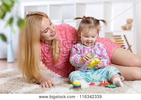 mother and her child playing with colorful puzzle toy