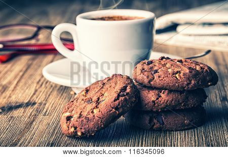 Cup of coffee with biscuit cookies and newspapper. Chocolate biscuit cookies. Chocolate cookies