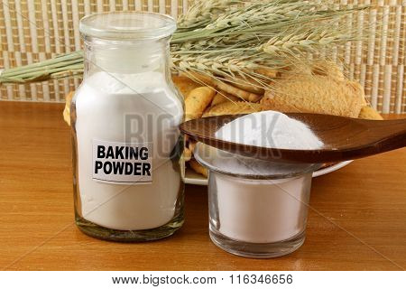 baking powder in a glass jar and wooden spoon with cookie and wheat