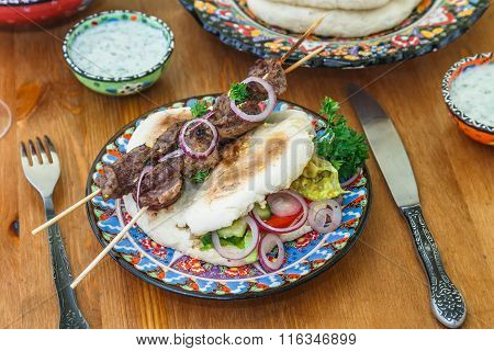 greek souvlaki served in a traditional way, on pita bread with onion rings and lemon