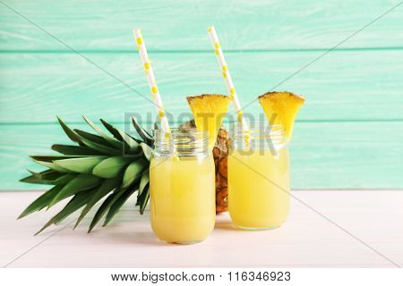 Bottles Of Pineapple Juice On A Pink Wooden Table