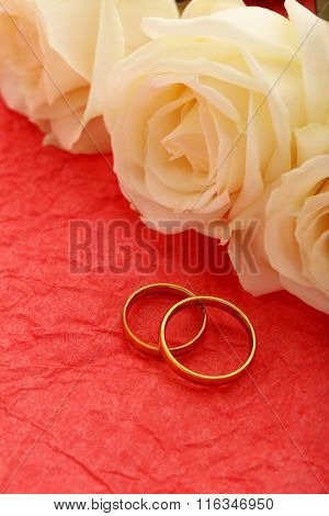 Golden Wedding Rings On A Red Paper Background