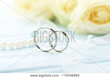 Silver Wedding Rings On A Blue Wooden Table