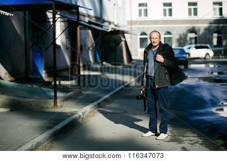 Brutal Street Photographer With Camera In Hand Strolling City Streets. Full Height Portrait. In Yard