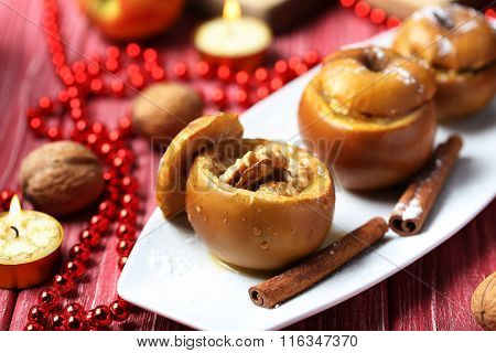 Baked Apples On Plate On Red Wooden Table