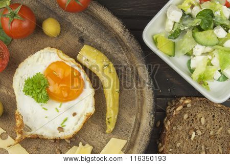 Fried Eggs on a wooden background. Fried eggs and vegetables on the cutting board.