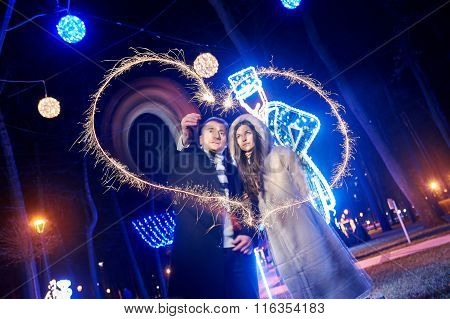 Happy Man And Woman Draw Heart Sparklers