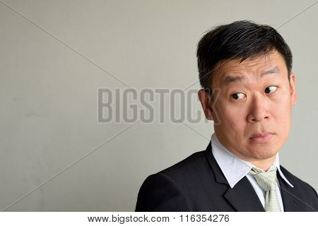 Mature Asian Executive Man looking suspiciously