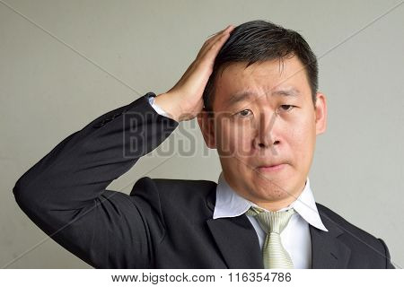 Mature Asian Man making a sad headache face