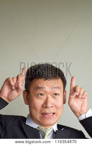 Mature Asian Man wearing suit smiling and have an idea