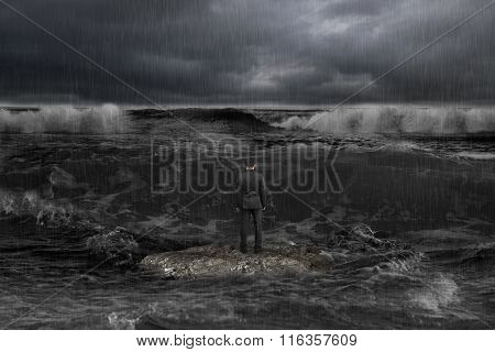 Businessman Standing On Rock Facing Oncoming Waves With Dark Ocean