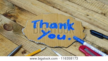 Thank you wording on cardboard on wooden background