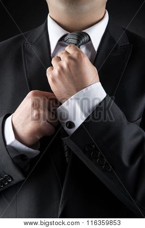 Businessman Correcting Tie