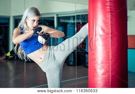Woman Hits The Heavy Bag With A Strong Kick