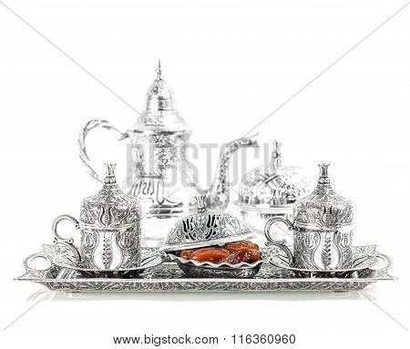 Table setting with silver tableware and dates. Oriental hospitality concept with tea or coffee cups. High key picture