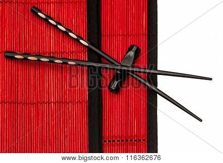 black chinese chopsticks on red bamboo mat. asian style table place setting
