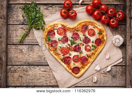 Heart shaped pizza with pepperoni, tomatoes, mozzarella, garlic and parsley composition on vintage w