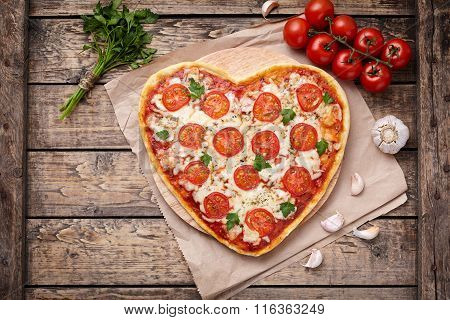 Heart shaped pizza margherita vegetarian love concept with mozzarella, tomatoes, parsley and garlic