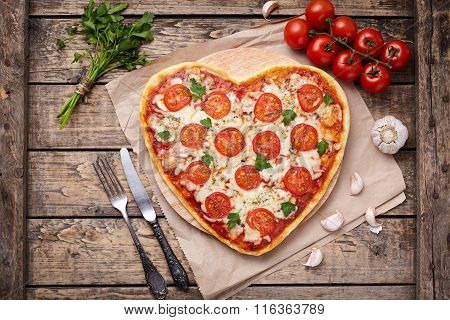 Heart shaped pizza margherita vegetarian love concept with mozzarella, tomatoes, parsley, knife, for