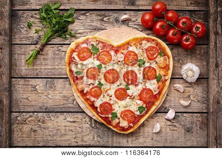 Heart shaped pizza margherita romantic love food concept with mozzarella, tomatoes, parsley, and gar