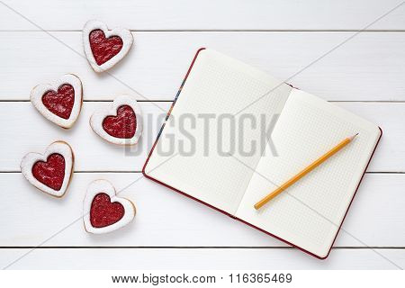 Heart shaped cookies with empty notebook frame and pencil composition for Valentines Day