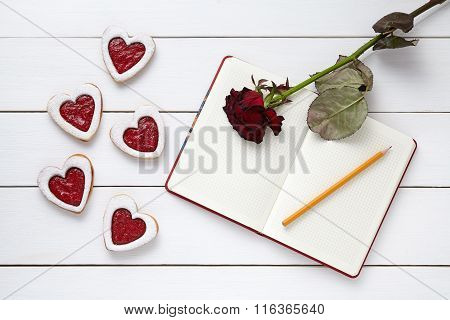 Homemade heart shaped cookies with empty notebook frame, pencil and red rose gift composition for Va