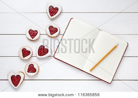 Heart shaped cookies with empty notebookand pencil on white wooden background for Valentines day