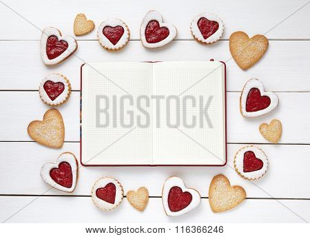 Empty notebook frame for design text and heart shaped cookies on white wooden background.