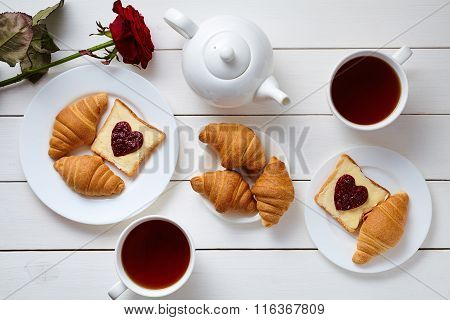 Breakfast for couple on Valentines Day with toasts, heart shaped jam, croissants, red rose flower an
