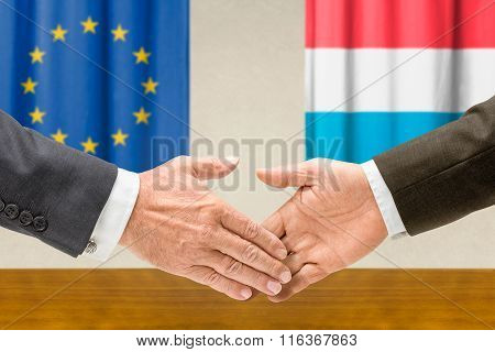Representatives Of The Eu And Luxembourg Shake Hands