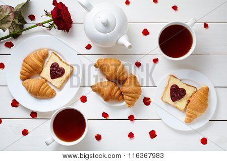 Breakfast for couple on Valentines Day with toasts, heart shaped jam, croissants, red rose flower, p
