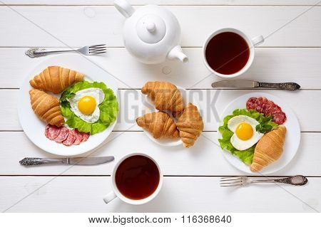 Heart shaped fried eggs, salad, croissants, salami sausage, composition and tea on white wooden tabl