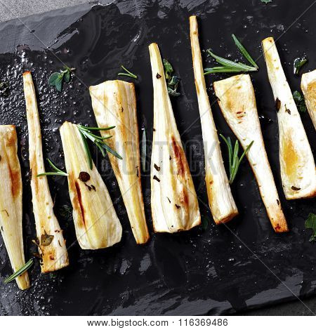 Roasted parsnips on slate.  Overhead view.