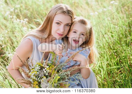 Mom and daughter in nature with a bouquet of wild flowers