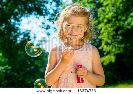 Beautiful Girl With Soap Bubbles In The Park