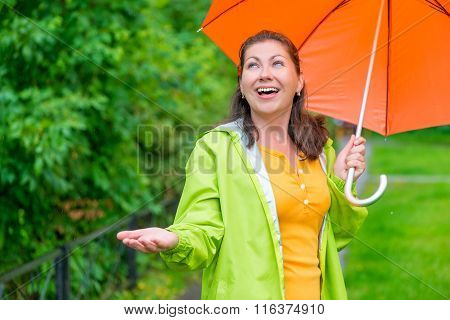 Happy Young Woman With A Bright Umbrella Waiting For The End Rain