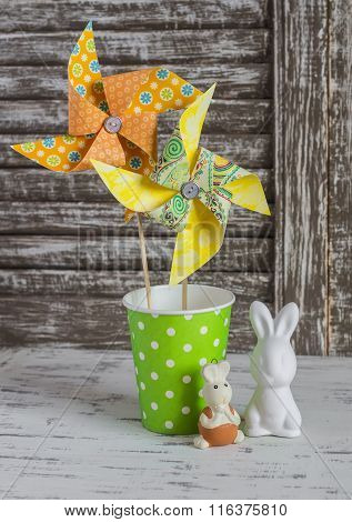 Homemade Paper Pinwheel, Ceramic Bunnies On A Light Rustic Wood Table. Easter Still Life In Vintage