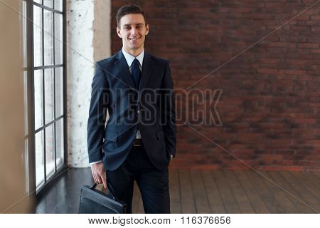 Portrait of businessman looking at camera, young successful male entrepreneur in suit.