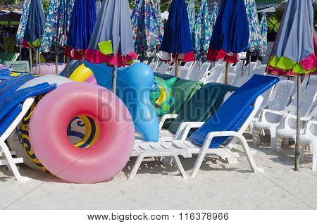 Sunbeds, Parasols And Rubber Rings On The Beach